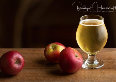 A chilled glass of cider with 3 fresh apples sitting next to the glass
