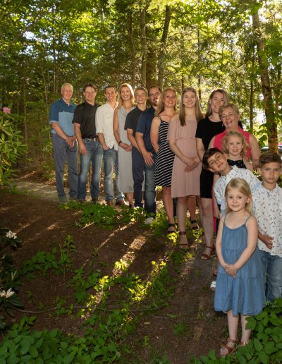 The whole Hockley family lines up in a curved row under the trees