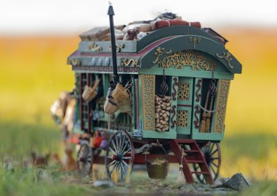 Freedom Miniatures Horse and Gypsey Wagon sitting in green grass with rolling hills in a burnt orange as the sun sets